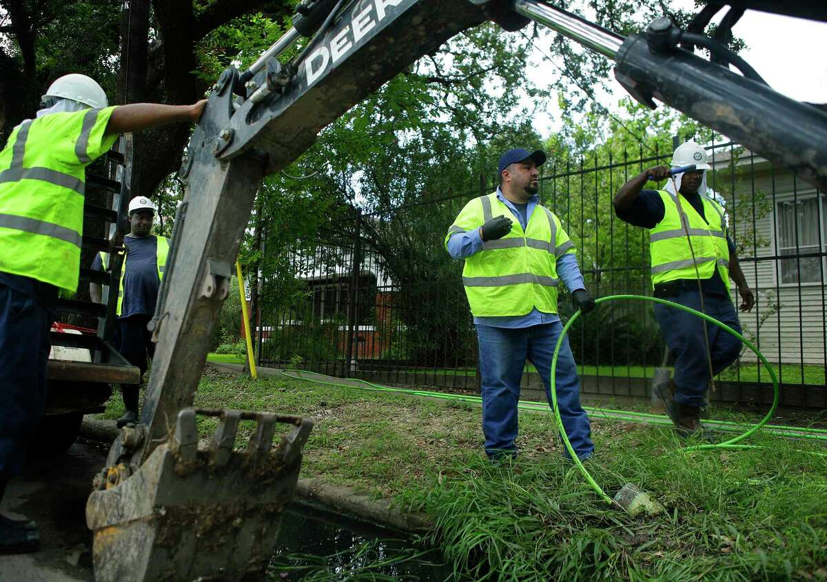 Utility worker Oswaldo Diaz (center) performs a trace on a service line to find a break in front of a house on Houston Avenue, Thursday, Aug. 25, 2016, in Houston. The crew found a hole in the service line where tree roots broke through it. ( Mark Mulligan / Houston Chronicle )