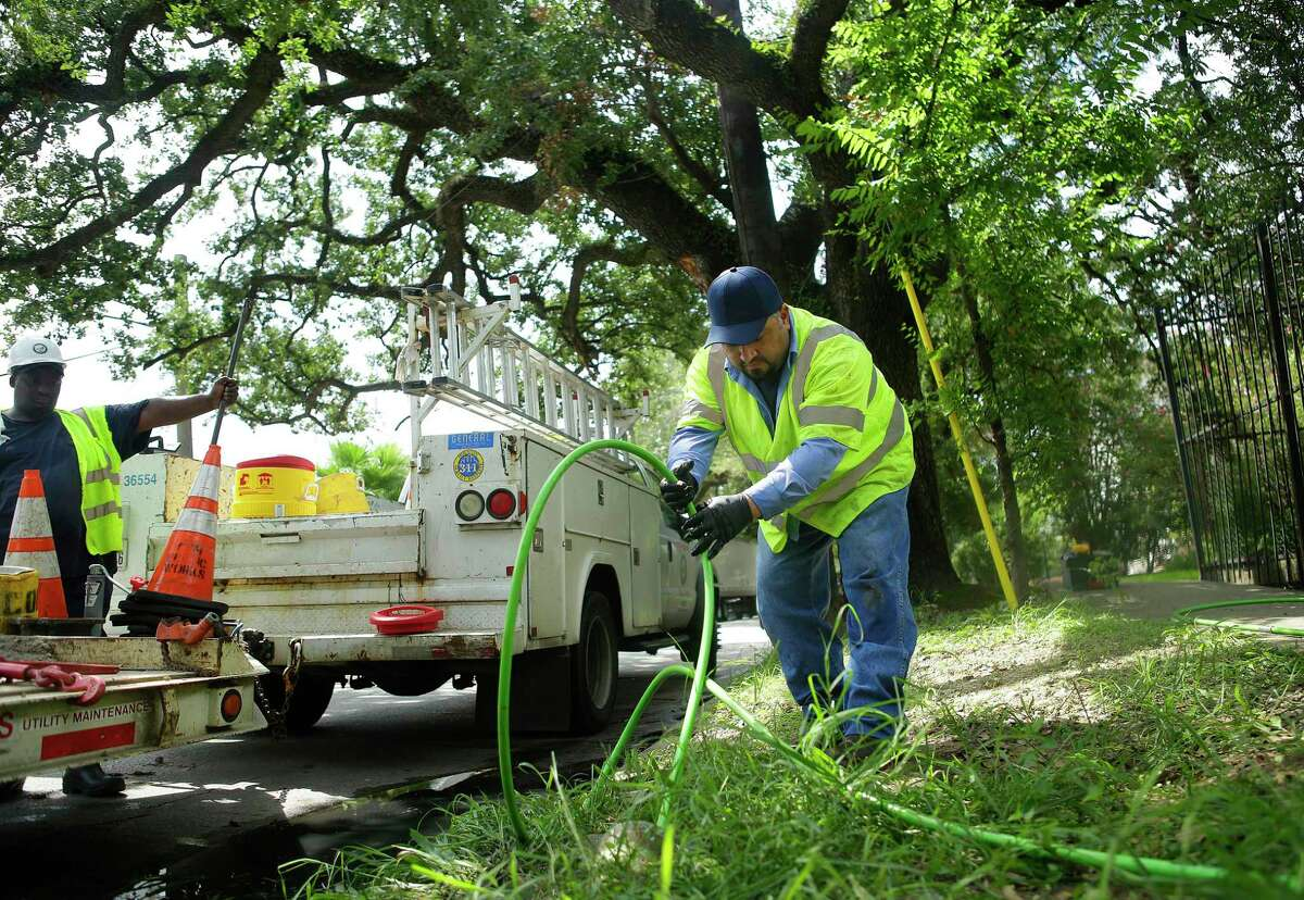 Utility worker Oswaldo Diaz (right) performs a trace on a service line to find a break in front of a house on Houston Avenue, Thursday, Aug. 25, 2016, in Houston. The crew found a hole in the service line where tree roots broke through it. ( Mark Mulligan / Houston Chronicle )