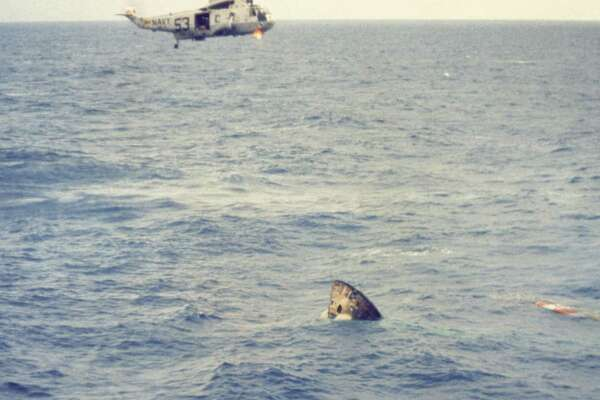 A recovery helicopter hovers above the Apollo 11 spacecraft seconds after it splashed down in the Pacific Ocean at 11:51 a.m. Houston time on July 24, 1969, about 900 miles southwest of Hawaii. The spacecraft turned apex down after impact, as shown here, but inflatable bags repositioned it shortly after this photo was taken.