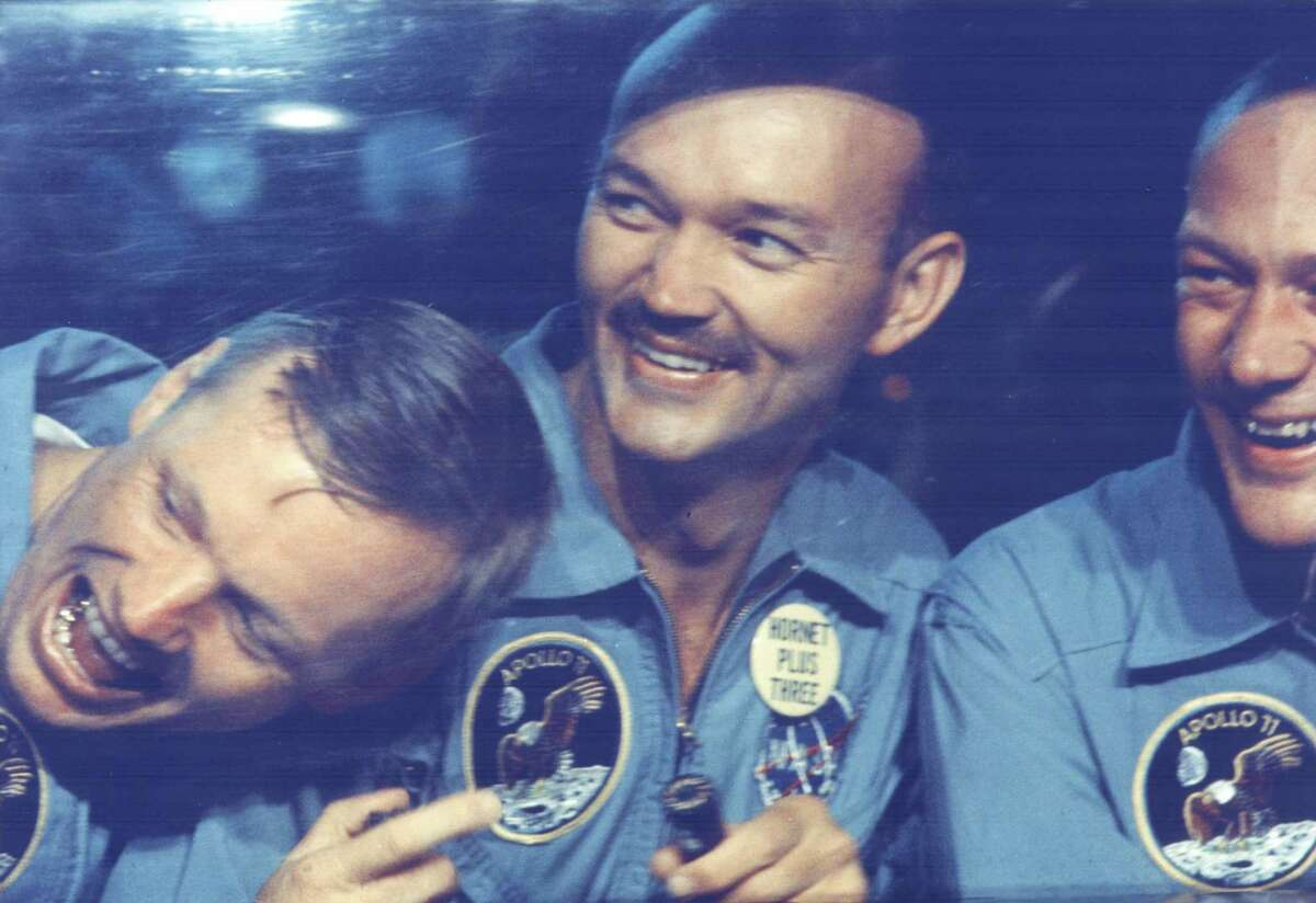 The Apollo 11 astronauts - (from left) Neil Armstrong, Michael Collins and Buzz Aldrin - share jokes with well-wishers from inside the Mobile Quarantine Facility aboard the USS Hornet. The astronauts splashed down at 11:51 a.m. Houston time at the completion of their historical eight-day lunar landing.