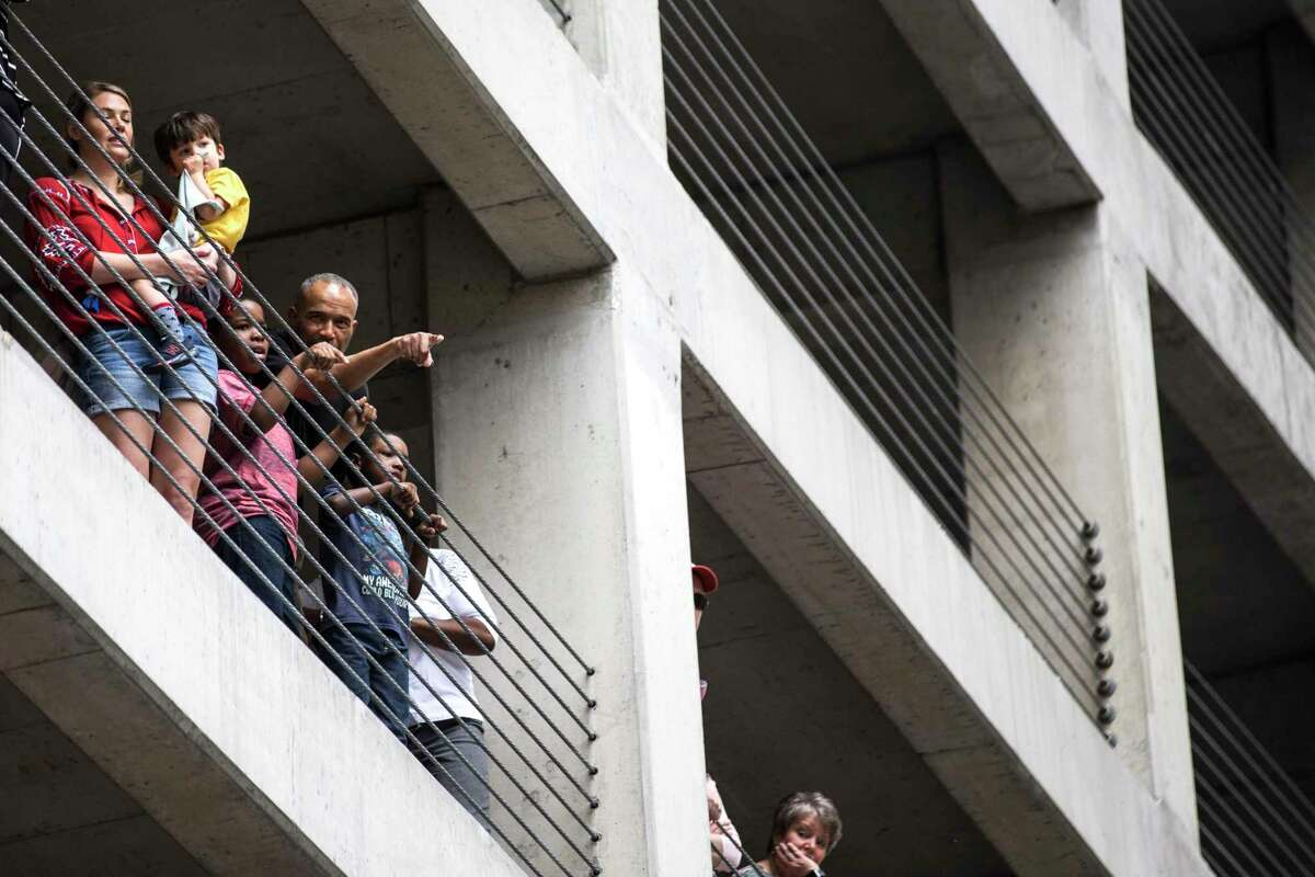 People watch the Houston Livestock Show and Rodeo Parade from a parking garage on Saturday, Feb. 24, 2018, in Houston. ( Brett Coomer / Houston Chronicle )