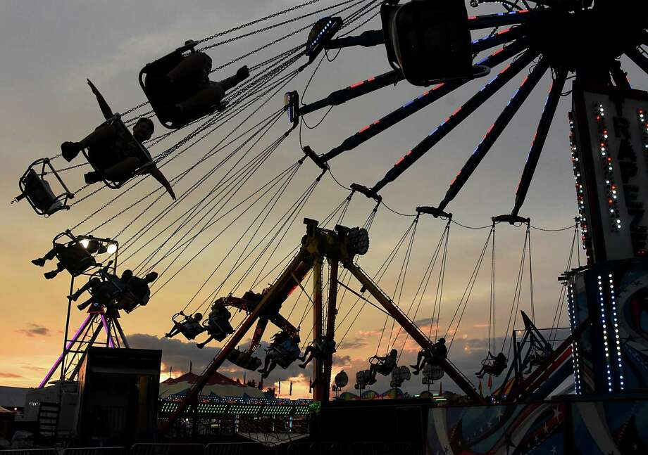 People take a ride on the Trapeze ride as the sun sets during the 178th Saratoga County Fair on Tuesday, July 23, 2019 in Ballston Spa, N.Y. (Lori Van Buren/Times Union) Photo: Lori Van Buren, Albany Times Union / 40047486A