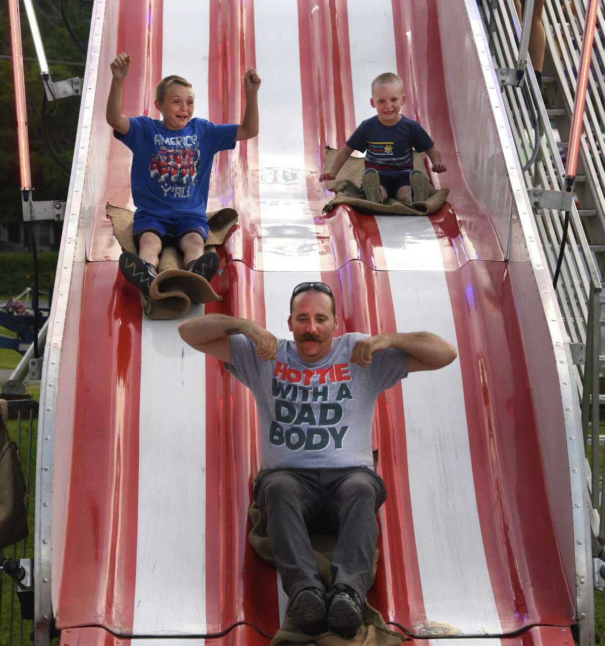 Sanford Perkins of Hudson Falls, center, goes down a slide with his son Noah, 5, on right, and Timothy Hall, 11, of Rotterdam, left, during the 178th Saratoga County Fair on Tuesday, July 23, 2019 in Ballston Spa, N.Y. (Lori Van Buren/Times Union)