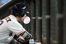 Houston Astros Josh Reddick (22) blows a bubble in the dugout during the second inning of an MLB baseball game at Minute Maid Park, Tuesday, July 23, 2019.