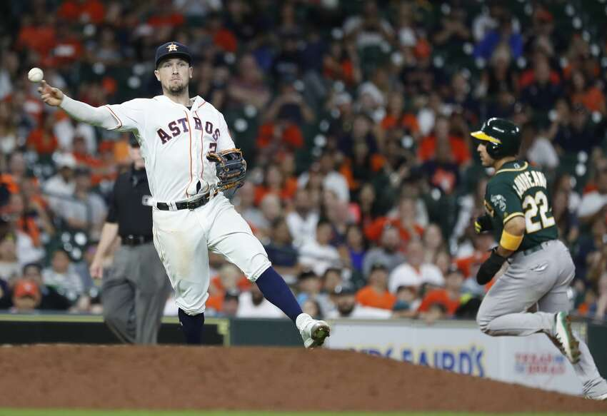 Houston Astros Alex Bregman (2) makes the throw to first base as Oakland Athletics Robbie Grossman ground out during the eleventh inning of an MLB baseball game at Minute Maid Park, Tuesday, July 23, 2019.