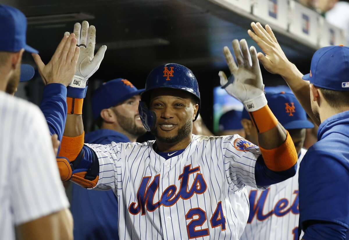 Teammates in the dugout congratulate New York Mets' Robinson Cano after the third of Cano's three home runs in a baseball game against the San Diego Padres, Tuesday, July 23, 2019, in New York. The last blast came against San Diego Padres relief pitcher Logan Allen in the seventh inning. It was the first time in Cano's long career that he has hit three home runs in one game. (AP Photo/Kathy Willens)