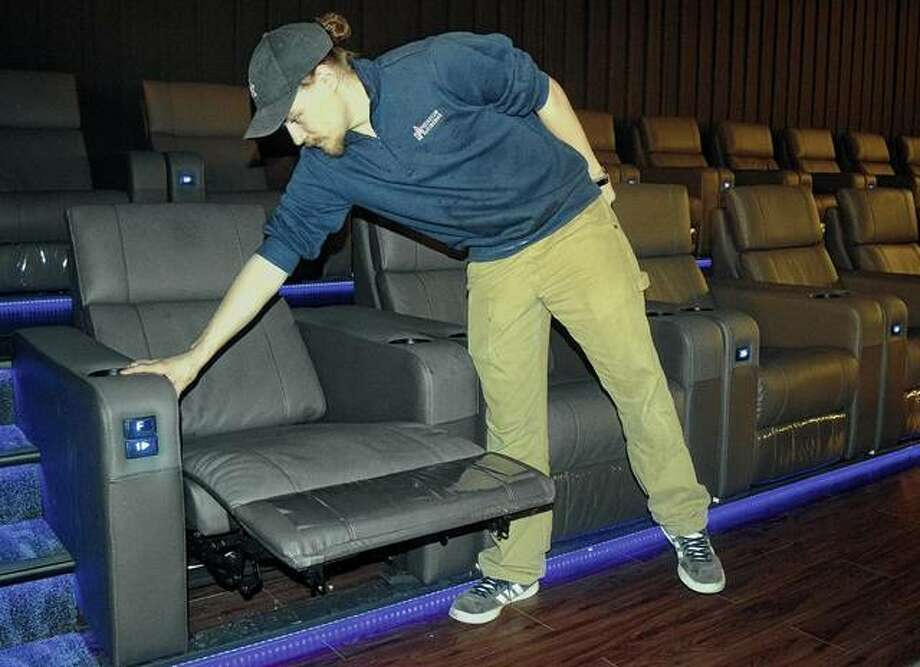 RMC Stadium Cinemas manager John Troxell demonstrates the recliner seats in the building's new theater.
