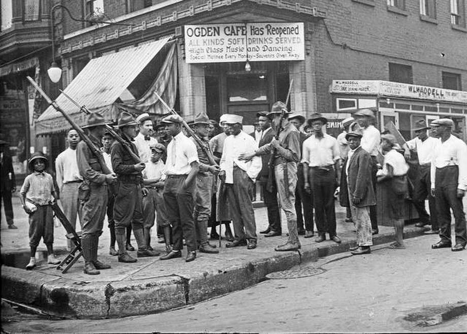 A crowd of men and armed National Guard stand in front of the Ogden Cafe during race riots in Chicago. Red Summer, as the summer of 1919 came to be known, saw white-on-black violence in big cities like Washington and Chicago and small towns like Elaine, Arkansas, and Bisbee, Arizona. Photo: Chicago History Museum | The Jun Fujita Negatives Collection Via AP