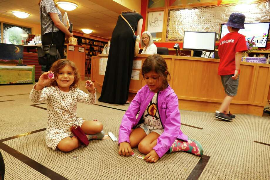 Serena Sordoni and her older sister Stella admire the button-like coins they earned as part of the Joust Read program at the New Canaan Library. They sat on the floor of the children's room on July 19. Photo: Grace Duffield / New Canaan Advertiser / Connecticut Post