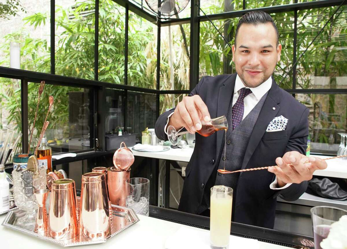 Bartender Jonathan Gallardo prepares a drink at the Secret Garden Bar in Bravery Chef Hall in Aris Market Square, 409 Travis, is shown Tuesday, July 23, 2019, in Houston.