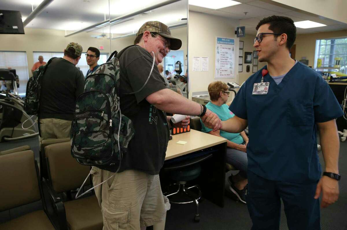 Schertz resident Amy Blair shakes hands with David Pena (right), a clinical exercise physiologist, as she departs from therapy at Christus Santa Rosa Rehab Services in New Braunfels on Friday, July 19, 2019. Blair had a default judgment issued against her for unpaid credit card debt. Blair suffers from pulmonary illness and fighting a rejection of a lung transplant from 2014. She medically retired as a police officer. (Kin Man Hui/San Antonio Express-News)