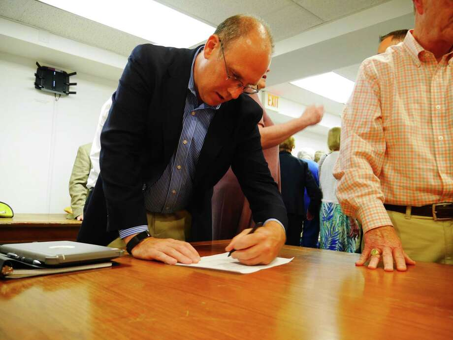 Republican nominee for the Ridgefield Board of Education Sean McEvoy signs his endorsement sheet Tuesday, July 23 Photo: Peter Yankowski