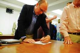 Republican nominee for the Ridgefield Board of Education Sean McEvoy signs his endorsement sheet Tuesday, July 23