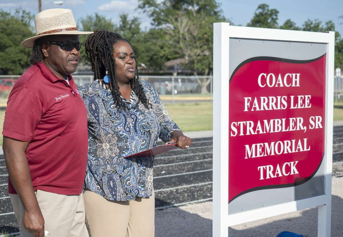 Jerry Strambler joins his niece, Tekeira Strambler Ray as she honors her late father, Farris Strambler, Sr. during the dedication ceremony 07/23/19 for the re-naming of the Lee High track, the Coach Farris Lee Strambler, Sr. Memorial Track. Tim Fischer/Reporter-Telegram