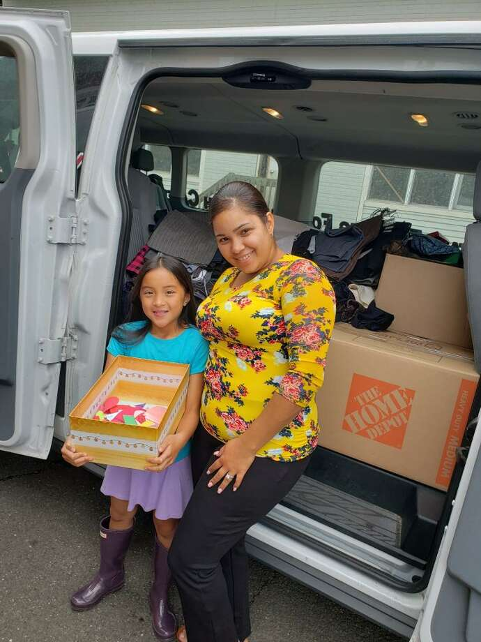 "Ridgefield Girl Scout Ruby Weiner presents donations to Grixaliz Montes of Dress for Success at the scouts end-of-year donation drive event on July 23. Ridgefield Girl Scouts filled a van with clothing, wrote ""Notes of Encouragement,"" and held the biggest donation drive to date for Dress for Success. Photo: Patty Labozzo / Contributed"