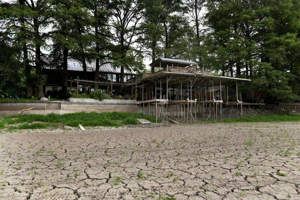 """A home sits next to the dry Lake Dunlap after a May dam failure. GBRA has announced plans to """"dewater"""" other lakes, citing concerns about other possible dam failures. It's the right call."""