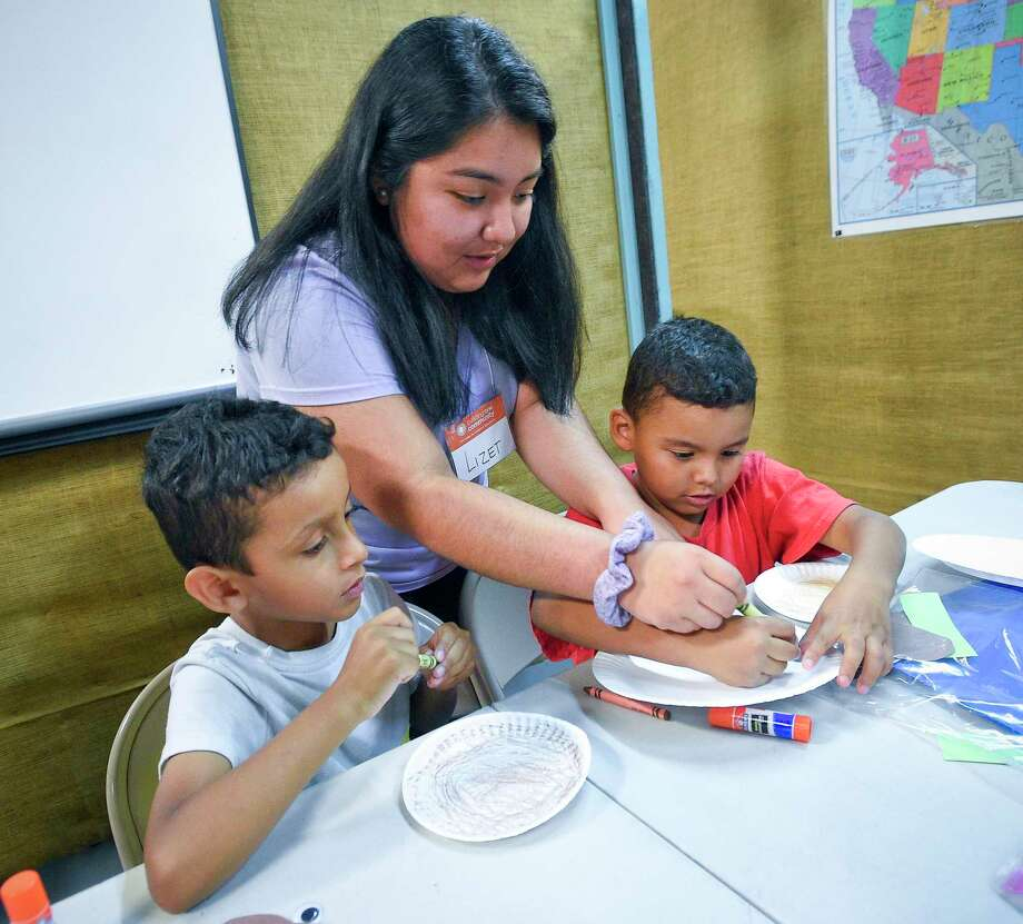 Volunteer Lizet Garcia, a Stamford High School Senior, works with Michael Martinez and his cousin Brian Martinez on an art project during a Summer Reading Program at Building One Community on July 23, 2019 in Stamford, Connecticut. Children and their parents took part in a month long reading program, designed to help prevent the Summer slide of reading and reading comprehension. The program in its 6th year, encourages parents to work with their child and pairs students in grades K-5 with volunteers with various activities to promote good literacy skills. Photo: Matthew Brown / Hearst Connecticut Media / Stamford Advocate