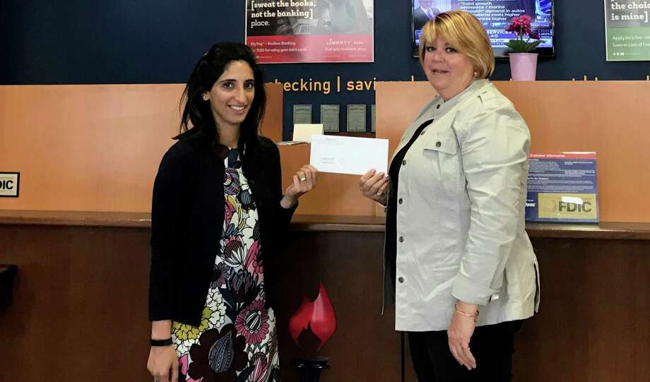 Toral Maher of the Liberty Bank Foundation gives Jane Michaud, executive director of Project Youth Court of New Haven, a check for $5,000. Photo: Contributed Photo