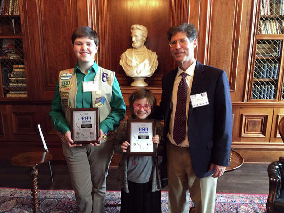 "Madison County Board Chairman Kurt Prenzler stands with Katharine Housewright and Riley Masinelli following the recent 35th annual Illinois Governor's Hometown Awards. Housewright received recognition for her ""Beautification of Triad Middle School Student Courtyard"" project. Riley accepted the award for her brother, who could not be present, for the wheelchair-accessible swing at Edwardsville Township Park. Photo: Summitted Photo"