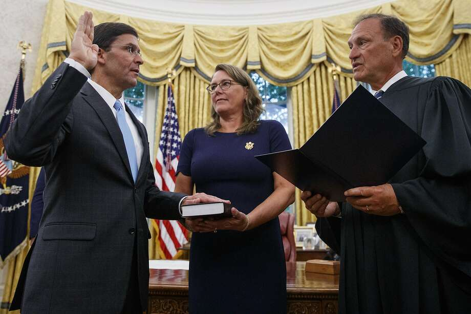 Mark Esper is sworn in by Supreme Court Justice Samuel Alito as his wife, Leah, holds a Bible at the White House. Photo: Carolyn Kaster / Associated Press