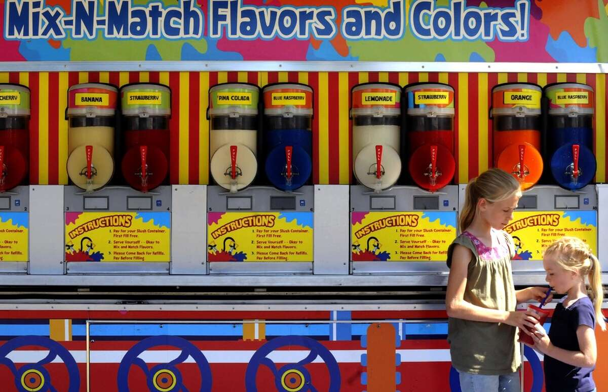 Eleven-year-old Samantha Neigh shares some of her mixed slushy drink with her sister Abigail Neigh during the Washington County Fair in Greenwich, NY Wednesday Aug. 22, 2012. The Washington County Fair said May 13, 2021 that it will reopen for the season after the pandemic. But said the state still needs to tell them how to operate. (Michael P. Farrell/Times Union)
