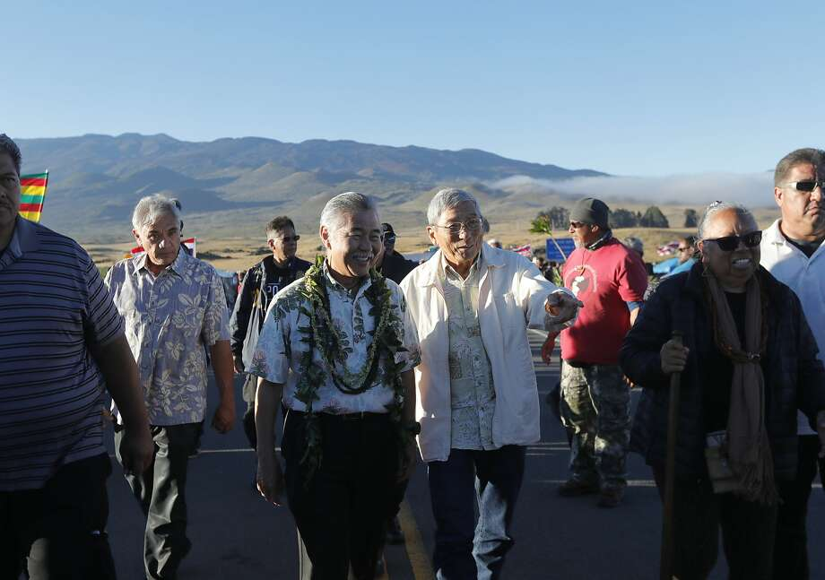 Hawaii governor David Ige (second from left) walks with Big Island Mayor Harry Kim at site of protesters blocking the construction of a giant telescope. Photo: Jamm Aquino / Associated Press
