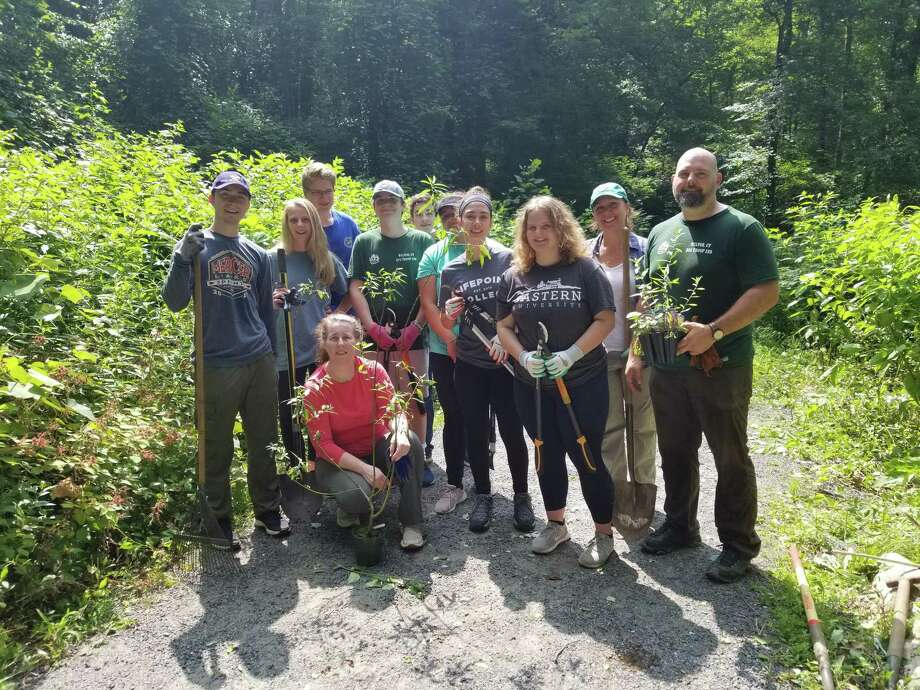 Seamus Masone, far left, with Scoutmaster Sean Heiligenthaler, far right and Assistant Scoutmaster Masone, in front. They are joined by Seamus' family, friends and fellow Scouts. Photo: Contributed Photo /Norwalk River Valley Trail