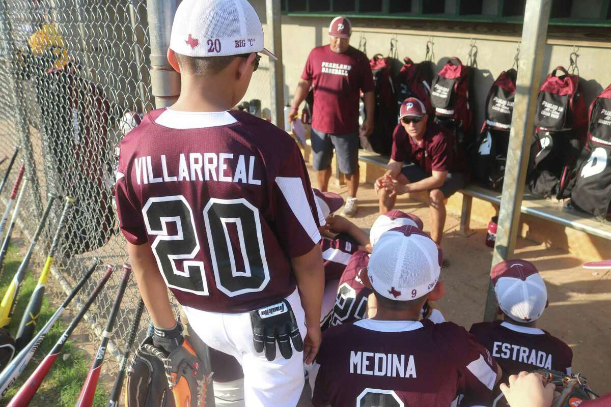 A member of the Pearland East 10s coaching staff talks to the team in the dugout prior to Tuesday night's state championship game in Tyler.