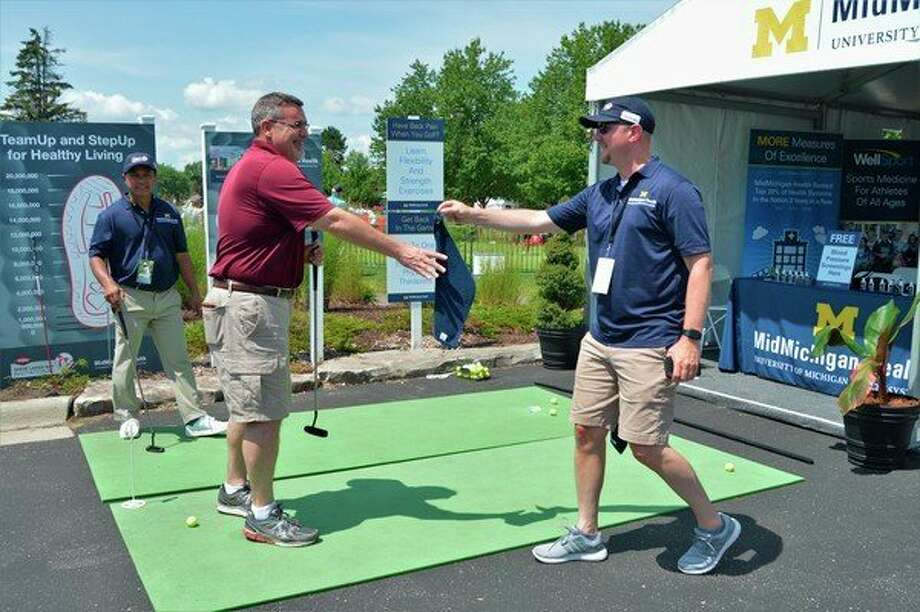 Tony Stamas, president and CEO of the Midland Business Alliance, putts a golf ball at the Mid Michigan Health tent at the Dow Great Lakes Bay Invitational on July 17, 2019. (Ashley Schafer/ashley.schafer@hearstnp.com)
