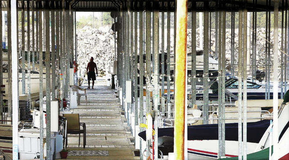 A man walks one of the walkways at the Alton Marina this week where most of the slips are full for the summer season.