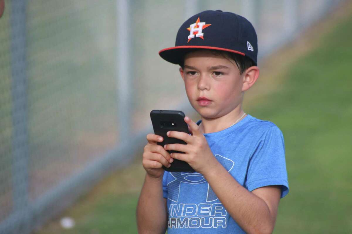 Deer Park Pinto All-Star second baseman Aysen Miller checks his cell phone to see if any college scouts texted him during the recent team's practice. Miller hopes the strong defense he showed in Texas will be on display in Louisiana this week.