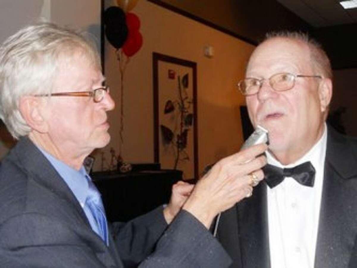 Karl DePew, of Mr. Karl's Hairdressing in Big Rapids, shaves Jack Batdorff at the Spring Artworks Gala. (Courtesy photo)