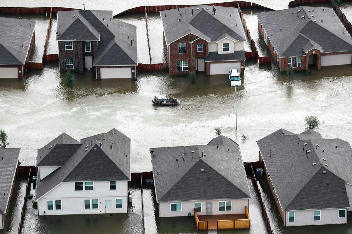 In Spring, a boat runs past houses flooded by Tropical Storm Harvey. (Brett Coomer / Houston Chronicle )