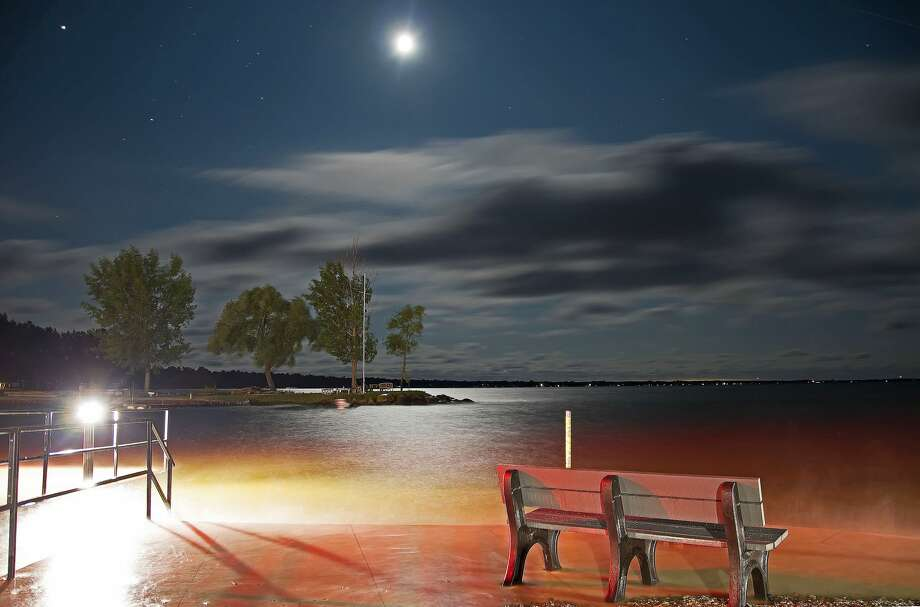 The moon shines down on the water at the mouth of the Pigeon River, at Pointe Park in Caseville on a recent summer evening. Photo: Bill Diller/For The Tribune
