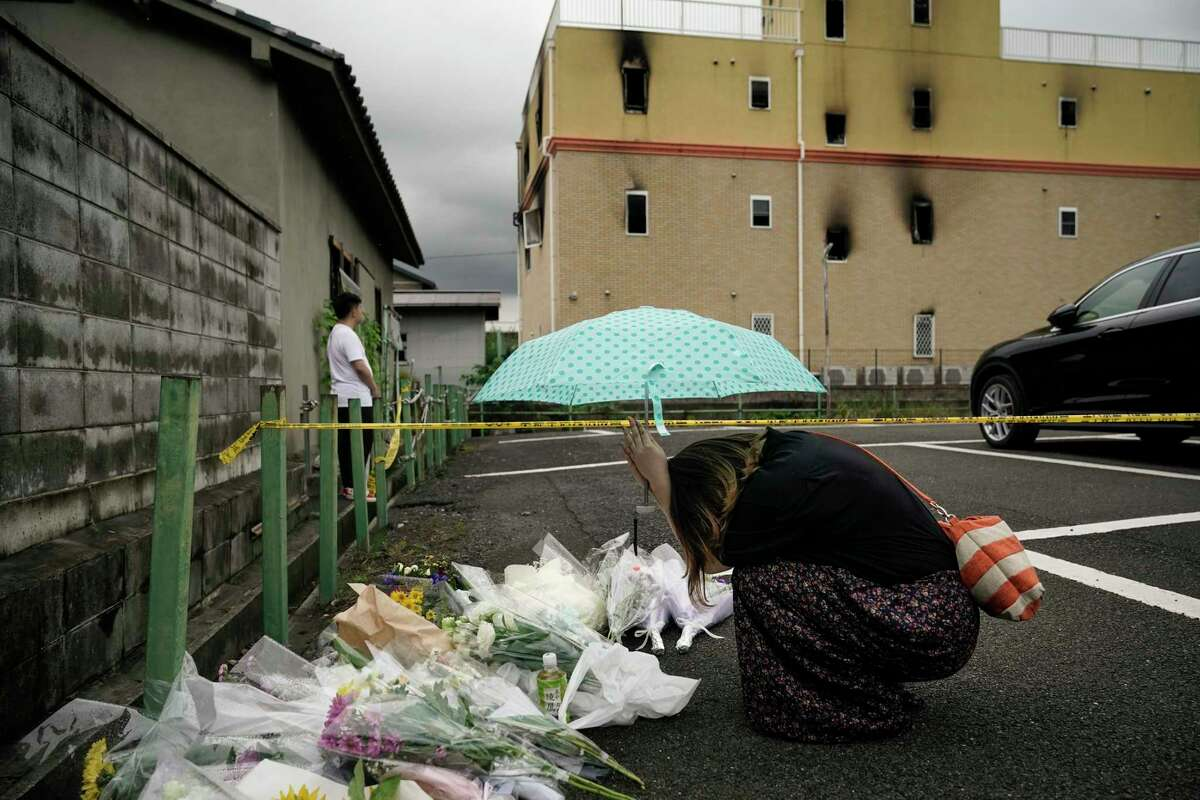 A woman prays at a makeshift memorial to honor the victims of Thursday's fire at the Kyoto Animation Studio building, background, Friday, July 19, 2019, in Kyoto, Japan. A man screaming