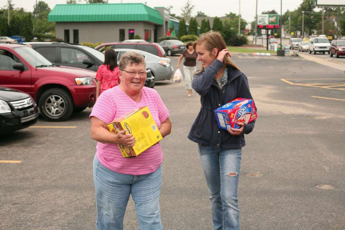 FOOD DONATION: Angels of Action volunteer Amanda Falk (right) helps carry boxes of food donated by Carol Kelley (left) during a food drive on Thursday at Family Video in Big Rapids. The event kicked off the nonprofit's summer food drive schedule. (Pioneer photos/Jonathan Eppley)