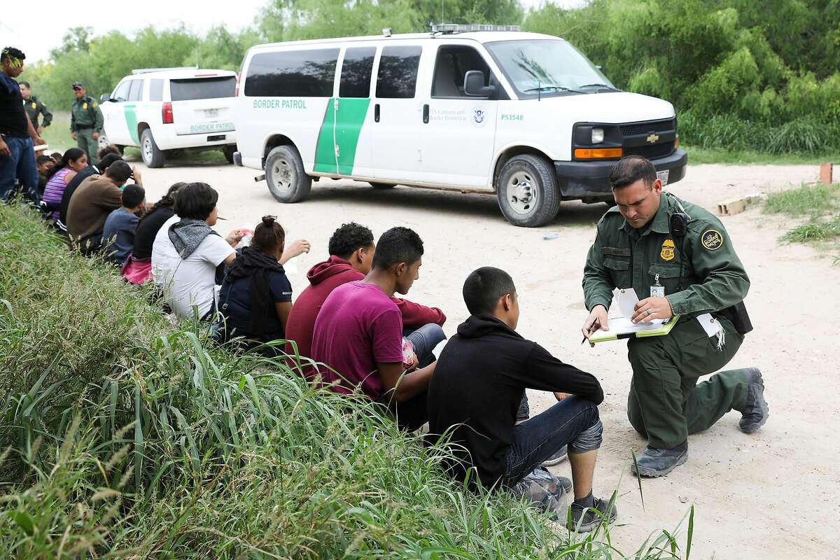 FILE-- A U.S. Border Patrol agent gathered information from migrants found near Granjeno, Texas, on April 12, 2019. A federal judge on July 24 let stand a new rule that bars migrants who failed to apply for asylum in at least one country on their way to the southwest border from obtaining protections in the United States, dealing the Trump administration a temporary win. (Eve Edelheit/The New York Times)