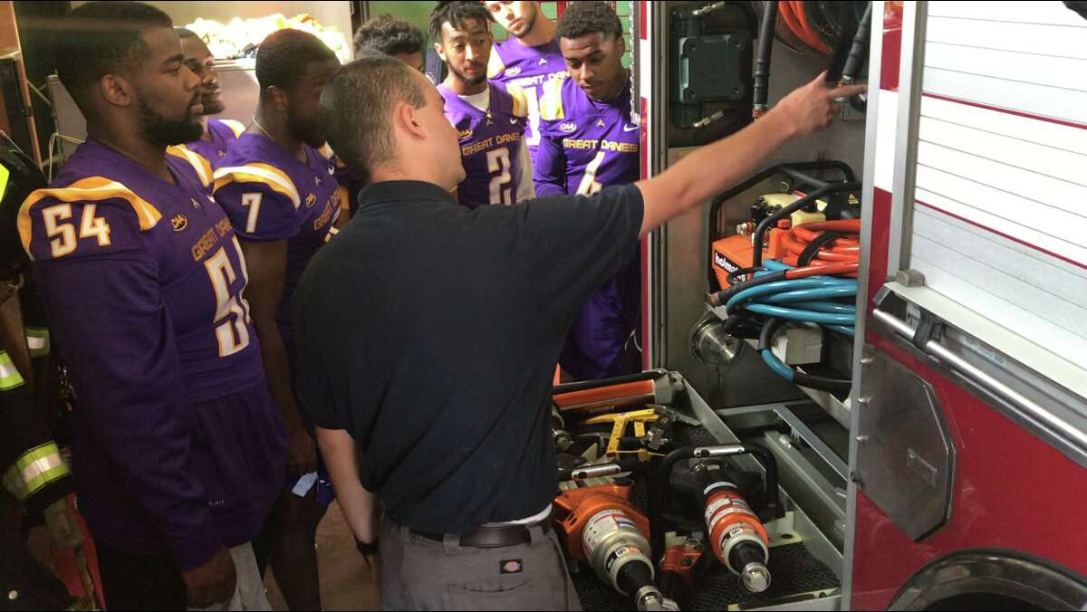 McKownville assistant fire chief Michael Costabile, pointing, shows UAlbany football players equipment on the fire truck on July 24, 2019. (Mark Singelais/Times Union)