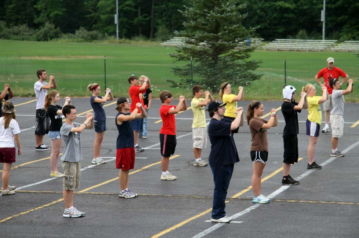 """photo_credit="""""""" IN STEP: The 70 members of Big Rapids High School's marching band complete drills on their first full day of band camp on Tuesday. (Pioneer photos/Lauren Fitch)"""