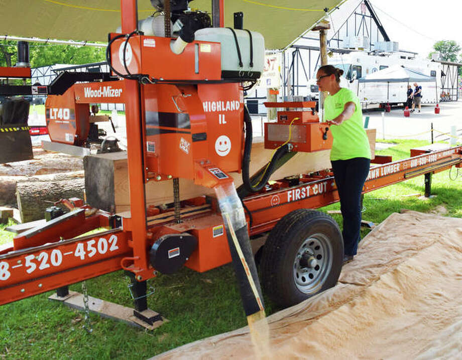 Valerie Elliott demonstrates how First Cut can make boards specific to their customer's needs using their portable sawmill at the 2019 Madison County Fair in Highland. Photo: Tyler Pletsch | The Intelligencer