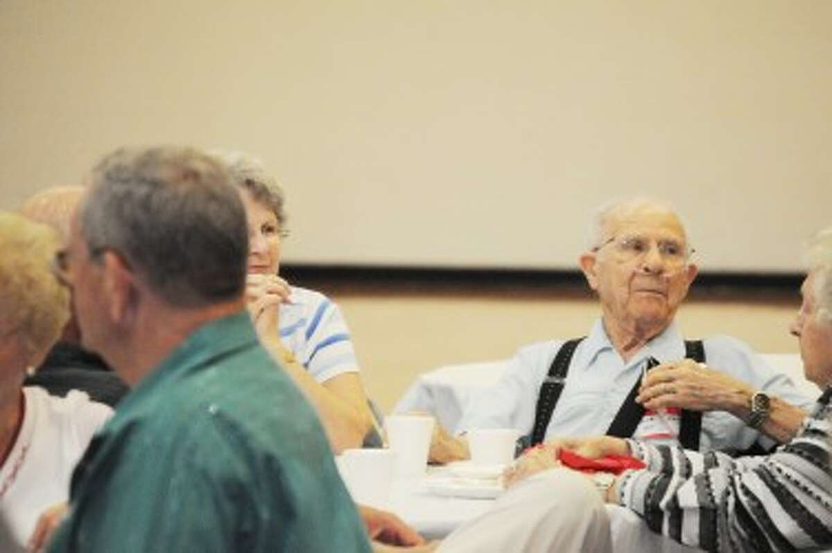 REMINISCE: Bob Winkler (right) listens to a speaker during the Big Rapids High School all-class reunion. Winkler and fellow classmate Alice Jensen graduate from the school in 1935, representing the oldest class in attendance at the reunion. (Pioneer photo/Kyle Leppek)