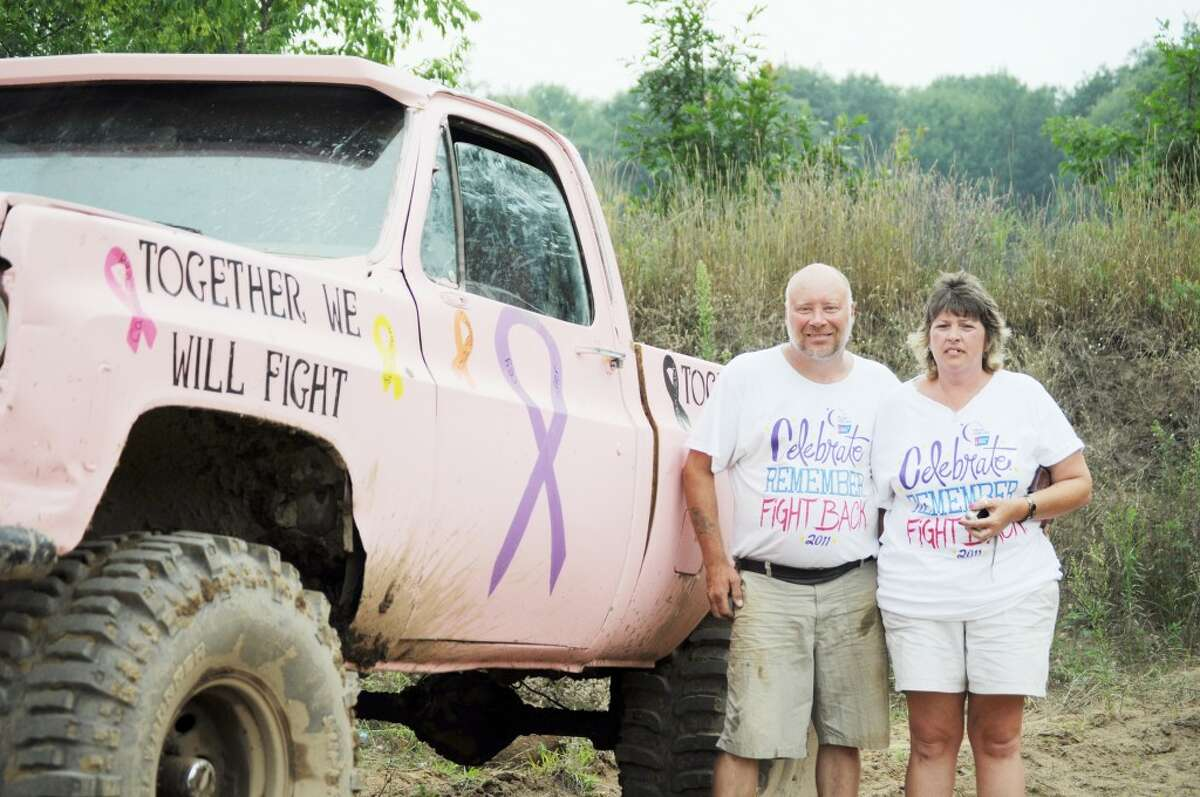 ORGANIZERS: Saturday's mud-run in White Lake was a fundraiser organized by the Cascade Fire Department to benefit the American Cancer Society. Henry Toppel (left) was approached by his cousin, a member of the fire department, to hold the event. His girlfriend, Tarra Stevens (right), painted their truck pink to support the cause. (Pioneer photo/Kyle Leppek)