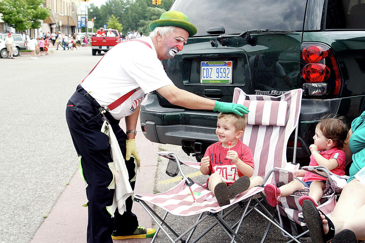 CLOWNING AROUND: Dynamite the Clown visits with children at the Reed City Great American Crossroads Celebration. This year's parade will take place at 6 p.m. on Friday, Aug. 14. (Pioneer file photo)