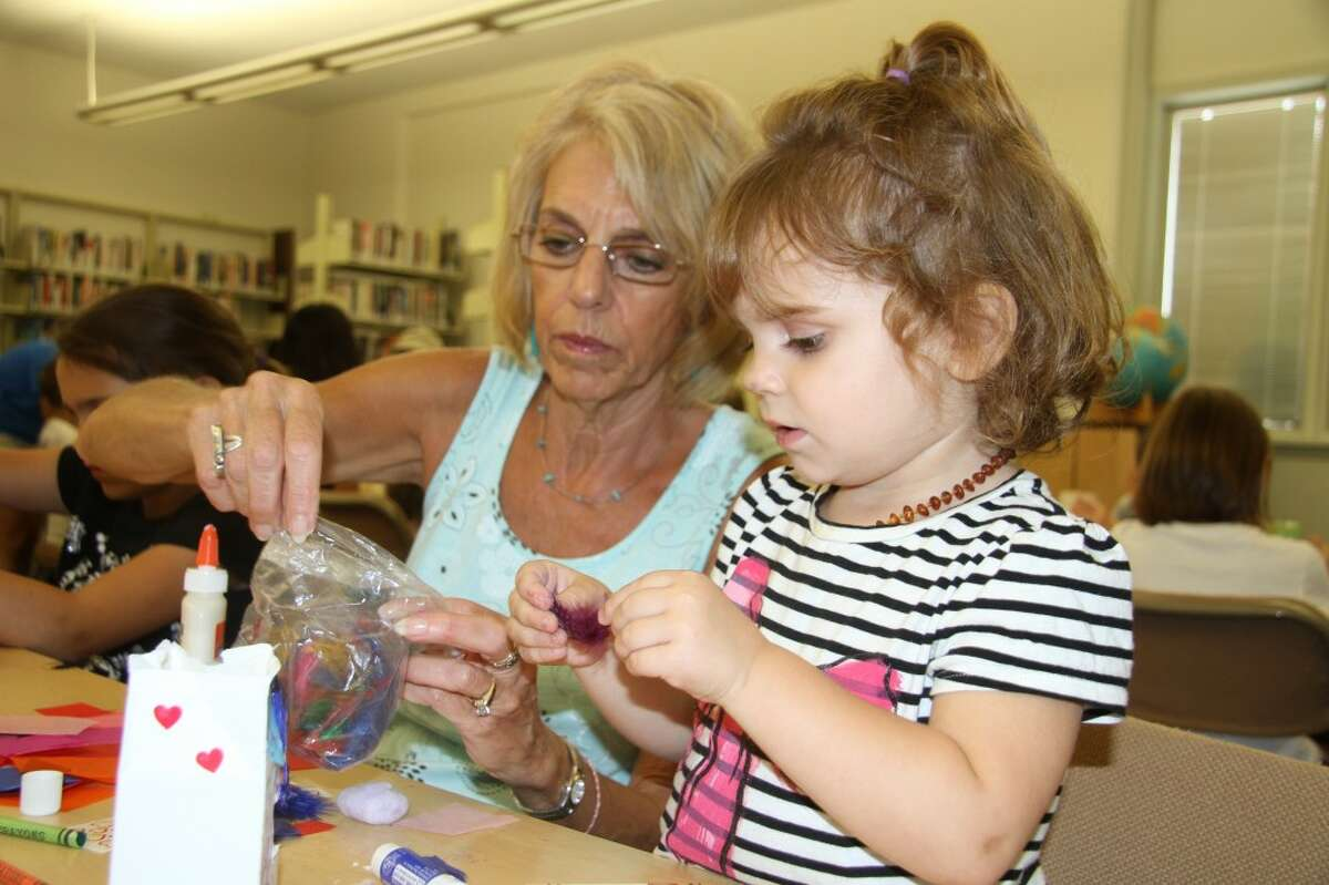 """photo_credit="""""""" A LITTLE HELP: Mary Jo Chaput helps her granddaughter, Myah Chaput, 2, pick out a feather to glue to her birdhouse. More than 25 children created birdhouses out of small milk containers on Tuesday at the Big Rapids Community Library. (Pioneer photos/Jonathan Eppley)"""