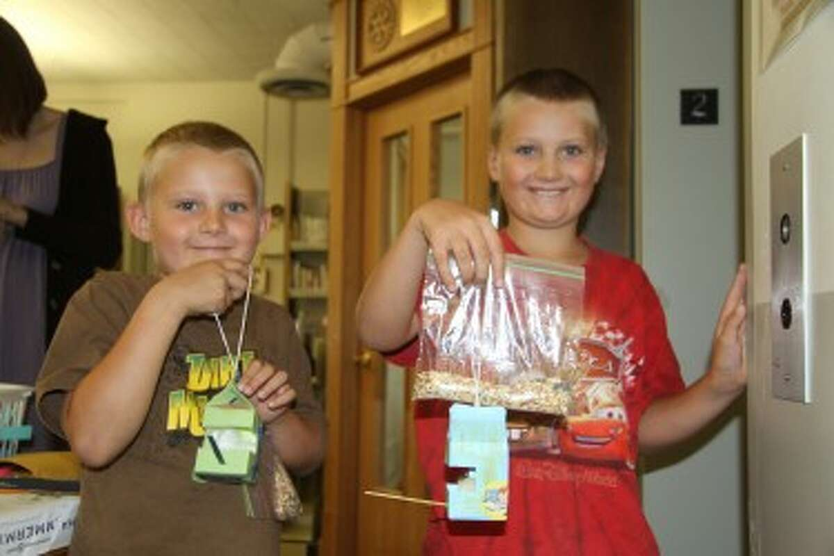 BIRDHOUSES: Brothers Isaac, 6, (left) and Joshua Anderson, 8, show off their completed birdhouses. More than 25 children decorated small birdhouses crafted from old milk containers.
