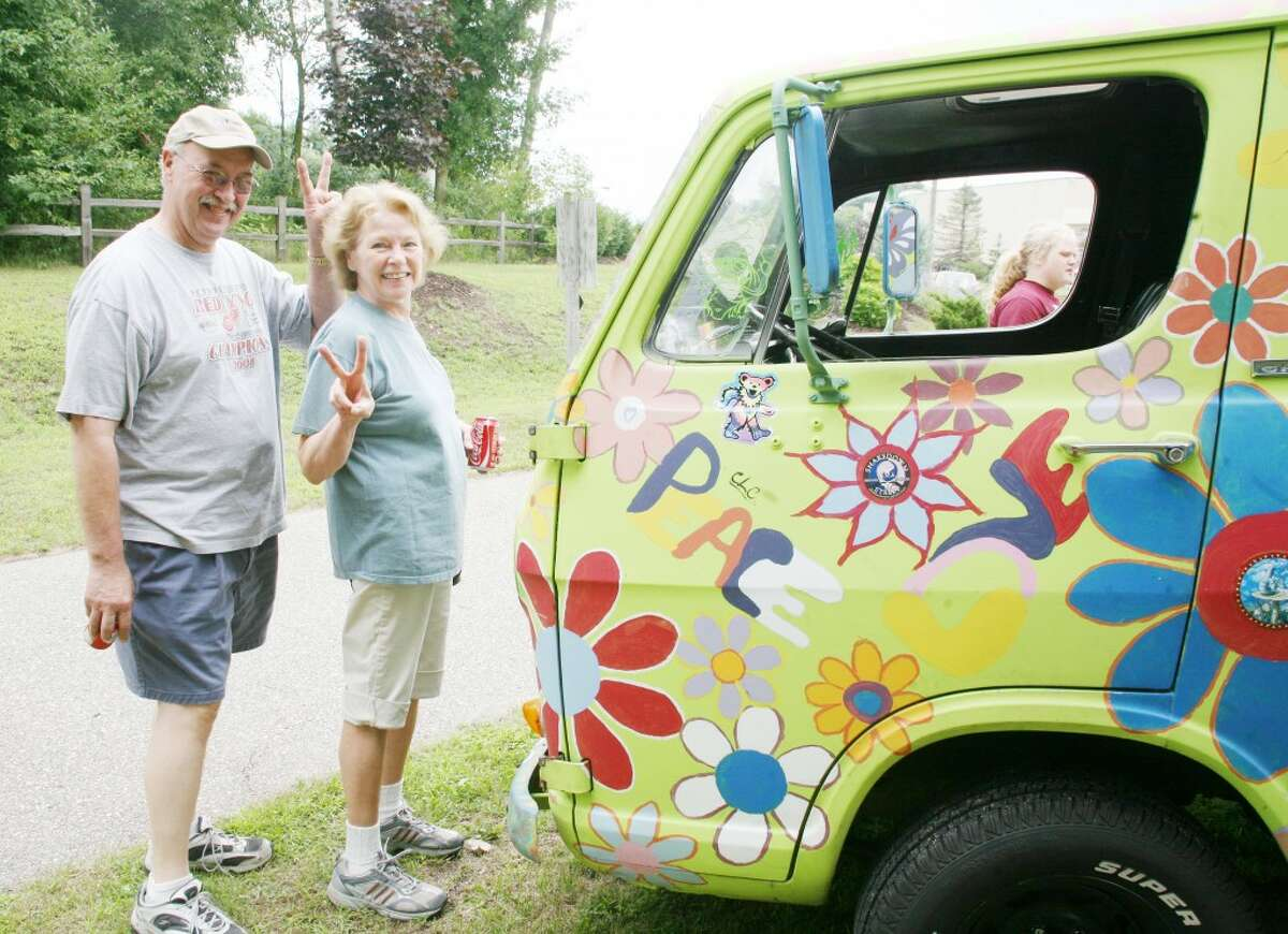 """PEACE: Nancy and Steve Squires, from Reed City, stand with Jeff Nelson's van at the Great American Crossroads Celebration car show. Nelson showcased his """"hippy van"""" at the festival for the second year. (Pioneer photos/Lauren Fitch)"""