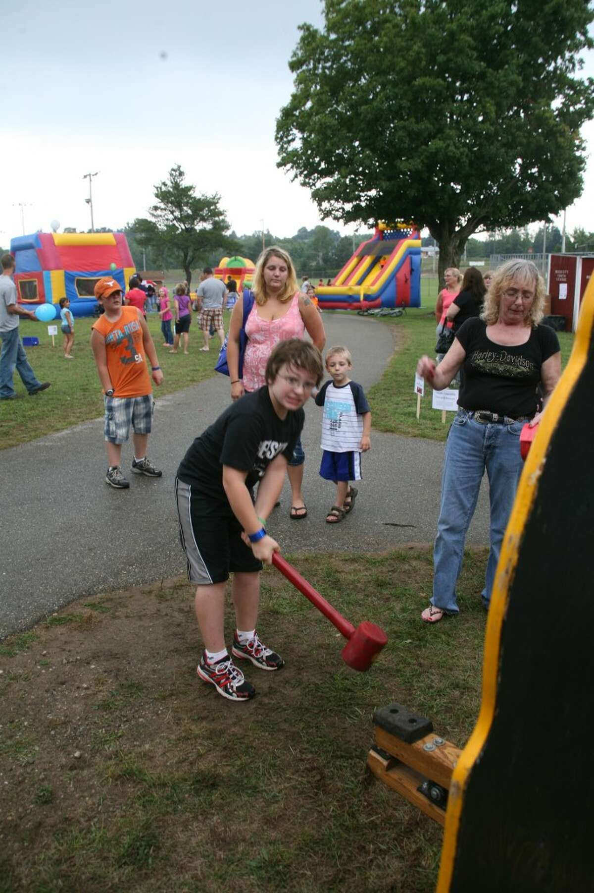 HAMMER TIME: A boy tries the sledge hammer game at the United Way and Yoplait Carnival, part of Reed City's Crossroads Celebration. The festival ran Wednesday through Sunday.