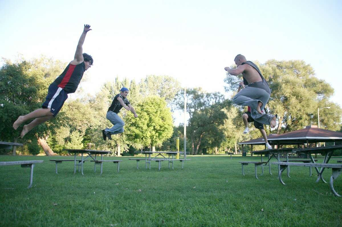 """photo_credit="""""""" ared Reed, Jacob Whitman, Katlin Reed and Mikeal Smith jump off a ring of picnic tables to land in the center, aiming to not crash into each other in the process. (Pioneer photos/Whitney Gronski-Buffa)"""