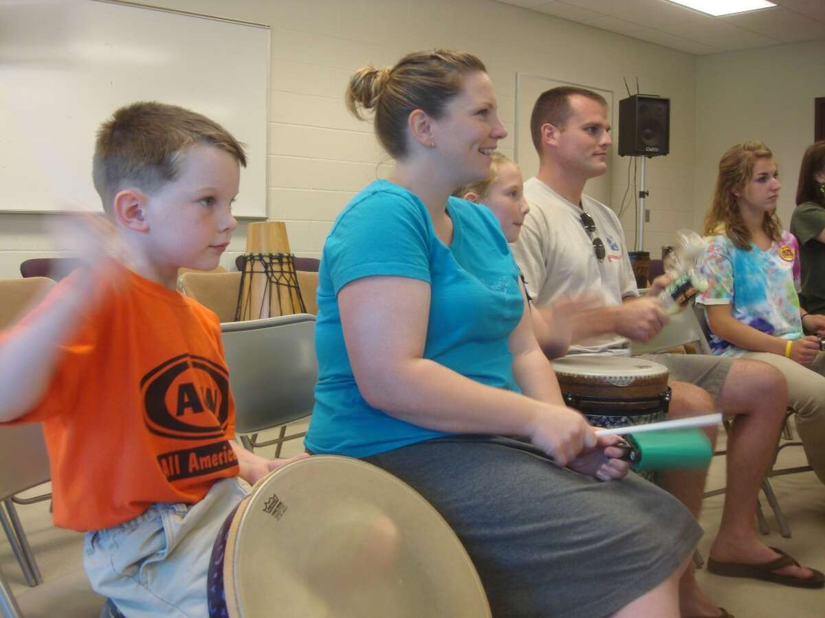 """FAMILY FUN: David Miller (left) bangs on a drum with his mother, Meaghan, sister, Chloe, and father, Mike. More than 40 people participated in a """"Drummunity"""" event on Thursday at the Department of Public Safety building."""