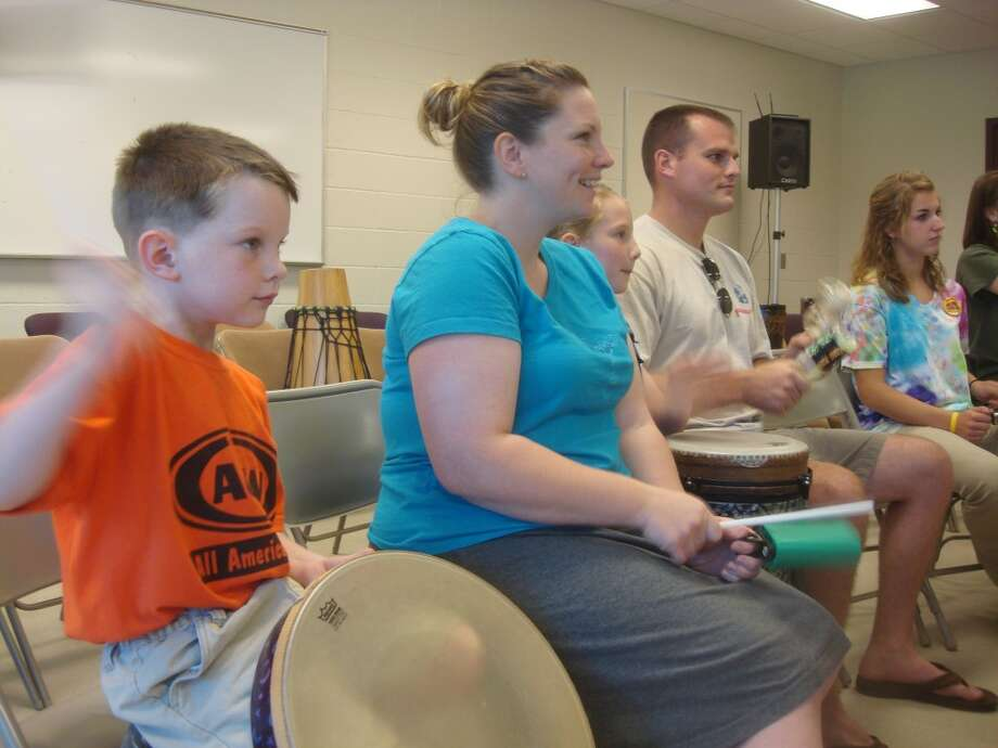 "FAMILY FUN: David Miller (left) bangs on a drum with his mother, Meaghan, sister, Chloe, and father, Mike. More than 40 people participated in a ""Drummunity"" event on Thursday at the Department of Public Safety building."